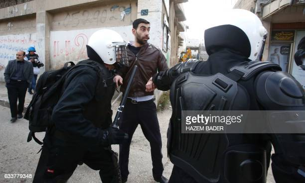 TOPSHOT Palestinian policemen arrest a demonstrator during a protest against a decision by the Palestinian Authority to grant a public land to the...