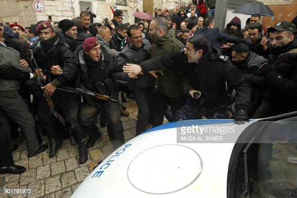 Palestinian policemen push away protesters from the convoy of Jerusalem's Greek Orthodox patriarch Theophilos III outside the church of Nativity in...