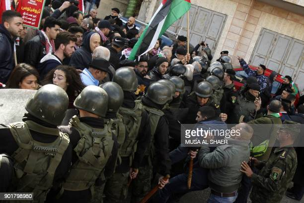Palestinian policemen push away protesters from the convoy of Jerusalem's Greek Orthodox patriarch Theophilos III in the West Bank town of Bethlehem...