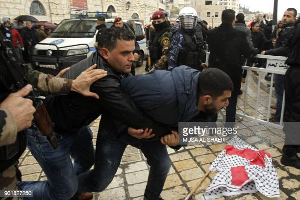 Palestinian policemen scuffle with protesters upon the arrival of the convoy of Jerusalem's Greek Orthodox patriarch Theophilos III in the West Bank...