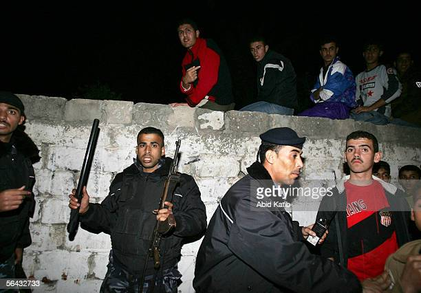 Palestinian policemen try to control the crowd after an Israeli missile strike on a car belonging to Khader Habib a political leader of the Islamic...