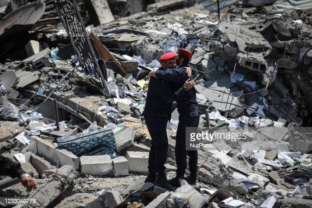 Palestinian policemen walk on the rubble of Arafat City, Gaza's police headquarters in Gaza City on May 22 following a ceasefire between Israel and...