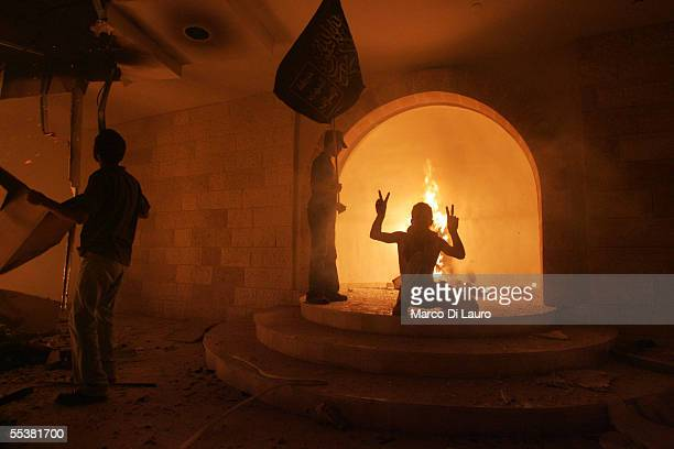 Palestinian poses at the site of the Jewish Torah into the Synagogue set on fire in Netzarim Settlement on September 12 2005 in the Gaza Strip...