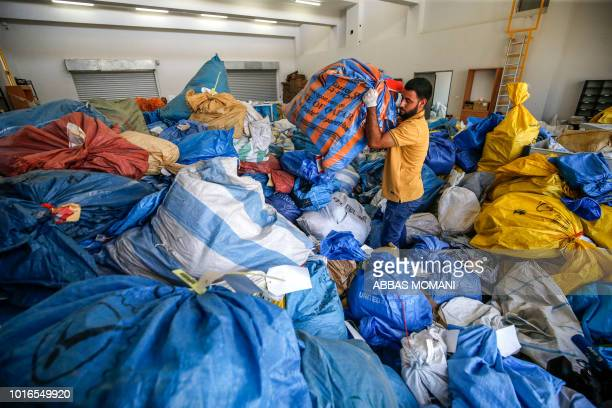 Palestinian postal worker sifts through sacks of previously undelivered mail dating as far back as 2010 which has been withheld by Israel at the...