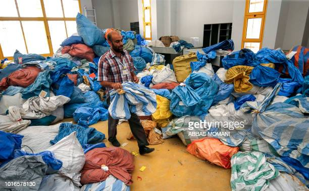 A Palestinian postal worker sifts through sacks of previously undelivered mail dating as far back as 2010 which has been withheld by Israel at the...