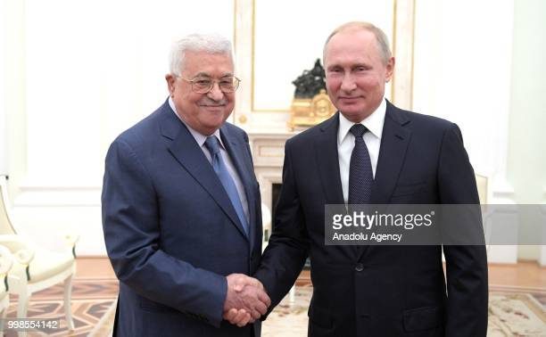 Palestinian President Mahmoud Abbas and President of Russia Vladimir Putin shake hands as they pose for a photo during their meeting at the Kremlin...
