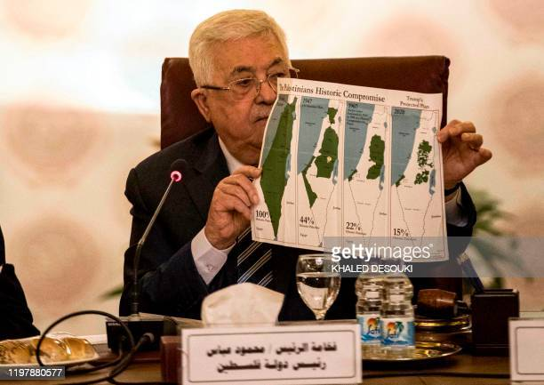 TOPSHOT Palestinian president Mahmud Abbas holds a placard showing maps of historical Palestine the 1947 United Nations partition plan on Palestine...