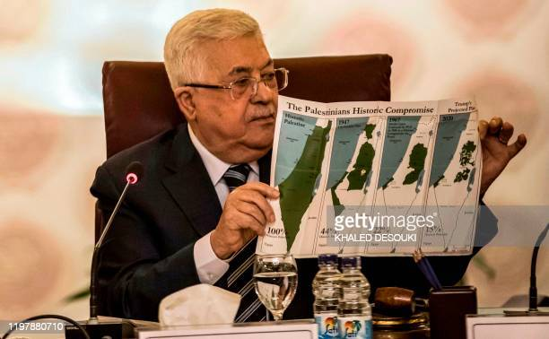 Palestinian president Mahmud Abbas holds a placard showing maps of historical Palestine the 1947 United Nations partition plan on Palestine the...