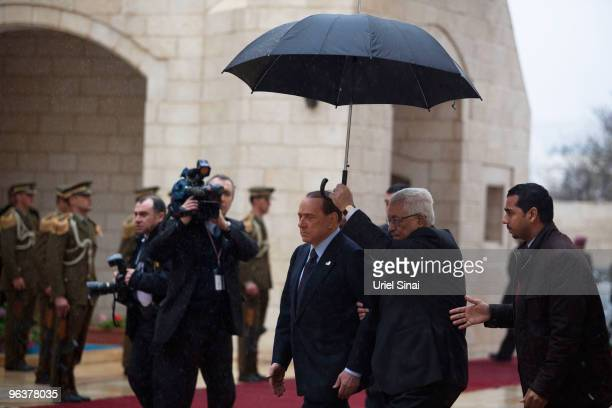 Palestinian President Mahmud Abbas holds an umbrella over himself and Italian Prime Minister Silvio Belusconi as they view an honor guard prior to a...