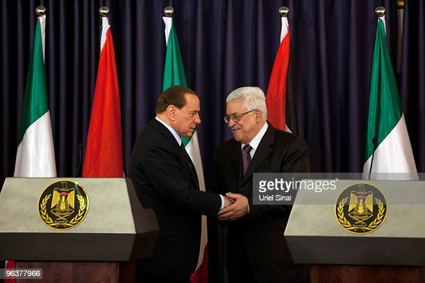 Palestinian President Mahmud Abbas shakes hands Italian Prime Minister Silvio Belusconi during a press conference at the Presidents compound on...