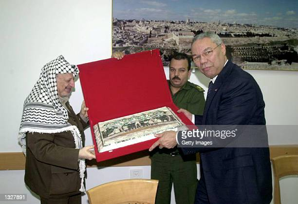 Palestinian President Yasser Arafat, left, presents an official gift June 28, 2001 to U.S. Secretary of State Colin Powell during talks in the West...
