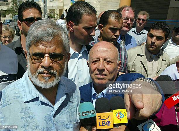 Palestinian prime minister Ahmed Qorei points towards the separation wall as he leads with Arun Gandhi the grandson of India's pacifist independence...
