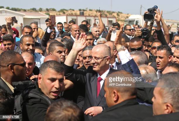 Palestinian prime minister Rami Hamdallah is surrounded by security as he waves following his arrival at the Erez border crossing in Beit Hanun in...