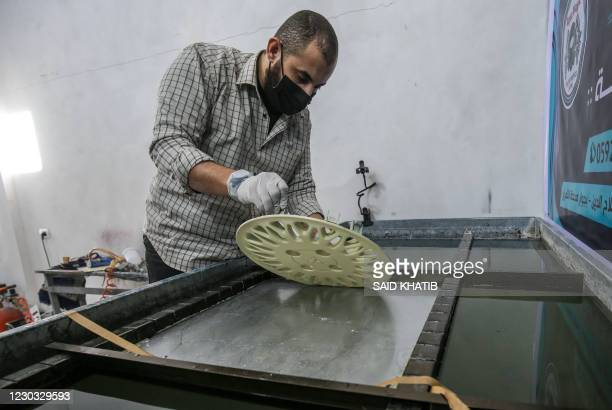 Palestinian printmaker Omar al-Asouli works on a piece at his water transfer printing workshop in Khan Yunis, in the southern Gaza Strip on December...