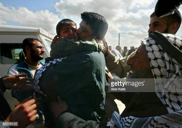 Palestinian prisoner Acarries his child as he arrives back home on February 21, 2005 in Jabalya refugee camp north of the Gaza Strip. Five hundred...