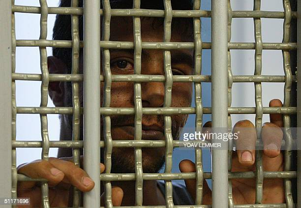A Palestinian prisoner held by Israel at the Rimonim Jail some 40 kms northeast of Tel Aviv peers through the bars of his cell 30 June 2004 Some 8000...