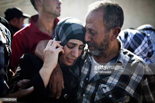 Palestinian prisoner hugs relatives as she speaks on a mobile phone after arriving in Mukata following her release on October 18 2011 in Ramallah...