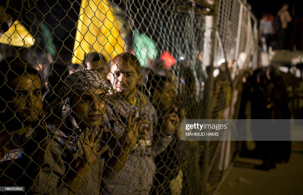 Palestinian prisoners' relatives wait behind a fence for their release at Erez point in the northern Gaza Strip on October 29, 2013. Israel freed 26 veteran Palestinian prisoners early on October 30, 2013 in line with commitments to the US-backed peace process, but moved in tandem to ramp up settlement in annexed east Jerusalem