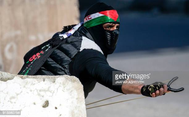 Palestinian protester aims a slingshot during clashes with Israeli soldiers following a demonstration near the Hawara checkpoint south of the West...