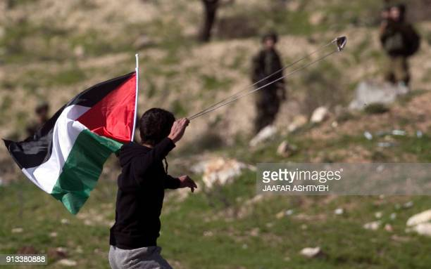 Palestinian protester aims a slingshot during clashes with Israeli soldiers following a demonstration near the Hawara checkpoint, south of the West...