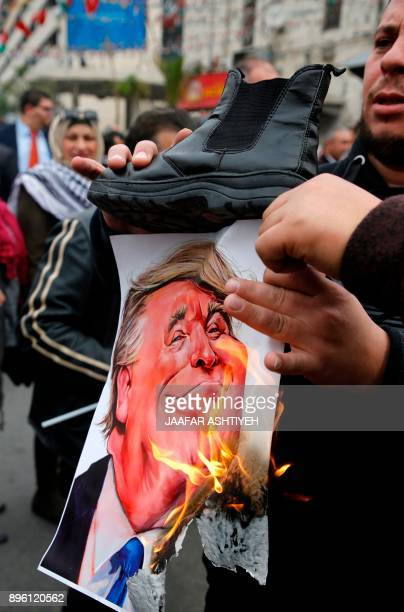 A Palestinian protester burns a cartoon of US President Donald Trump with a boot placed above it during a demonstration in the city of Nablus in the...