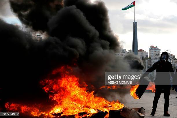 A Palestinian protester burns tyres during clashes with Israeli troops following a protest against US President Donald Trump's decision to recognize...