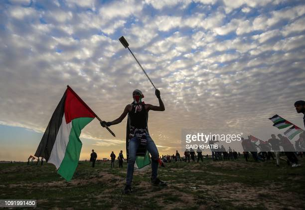 Palestinian protester carries a national flag and a slingshot during a demonstration near the fence along the border with Israel east of Gaza City on...