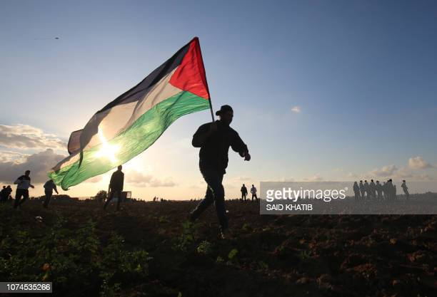 Palestinian protester carries a national flag during a demonstration near the border between Israel and Khan Yunis in the southern Gaza Strip on...