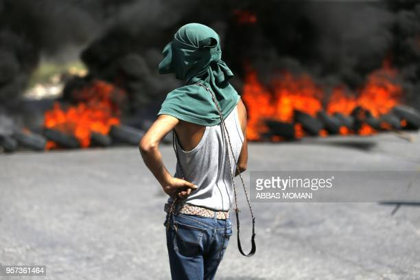 Palestinian protester carries a slingshot as he stands behind burning tyres during clashes between Paletenians and Israeli soldiers ahead of the 70th...