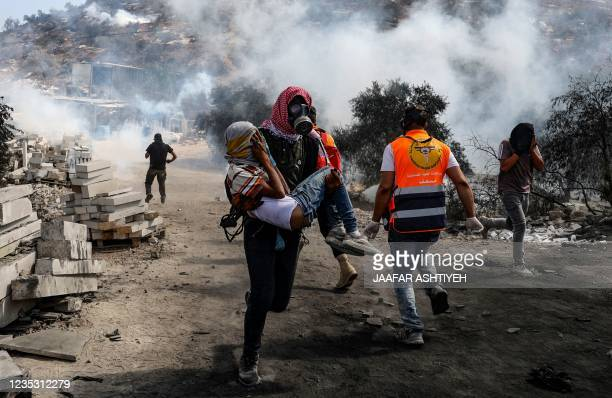 Palestinian protester carries a young man away from the scene of confrontations with Israeli security forces, following a demonstration against...