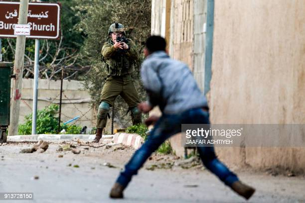 Palestinian protester confronts an Israeli soldier during an army search operation in the Palestinian village of Burqin in the northern occupied West...
