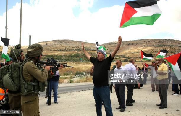 A Palestinian protester confronts Israeli soldiers during a demonstration in support of prisoners refusing food in Israeli jails at the Hawara...