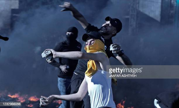 Palestinian protester confronts Israeli troops at the Hawara checkpoint south of Nablus city in the occupied West Bank on May 18 during a...