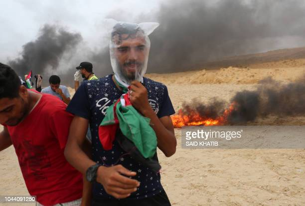 Palestinian protester covers his head with a plastic bag to protect himself from tear gas during a demonstration on the beach near the maritime...
