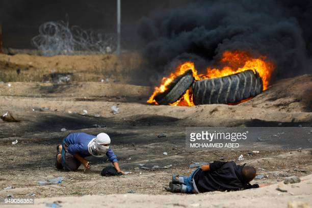 Palestinian protester crawls to help a comrade past burning tires during clashes with Israeli forces across the border following a demonstration...