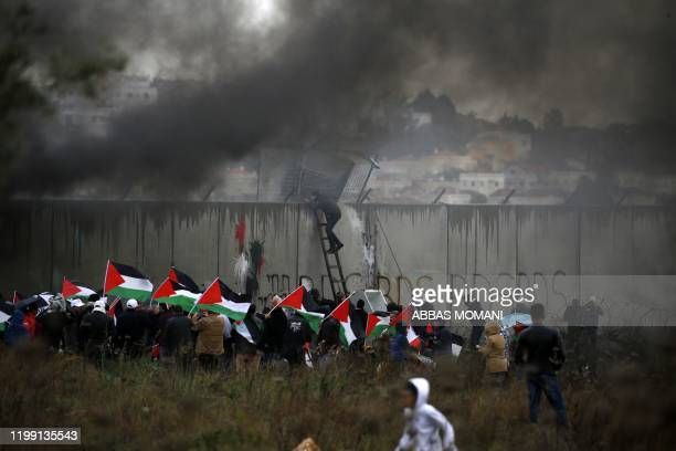 Palestinian protester escalates Israel's controversial security wall as others waving national flags burn tyres during a demonstration against a...