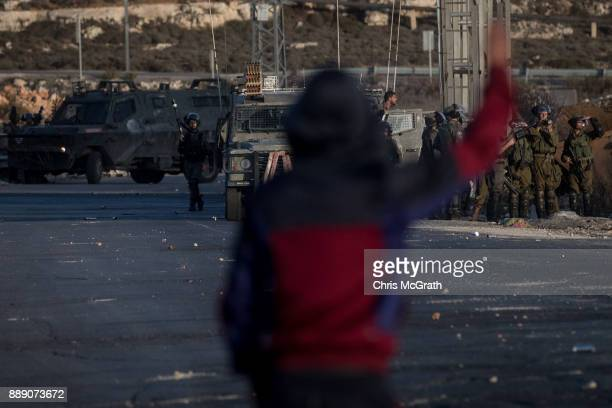 Palestinian protester gestures to Israeli border guards during clashes near an Israeli checkpoint on December 9 2017 in Ramallah West Bank Protests...