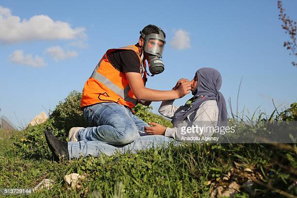 Palestinian protester helps his friend during a protest against Israeli violations in West Bank and Damascus in front of Ofer prison in the west of...