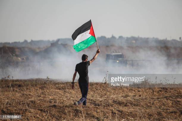 Palestinian protester holding Palestinian flag during clashes with Israeli troops following the tents protest where Palestinians demand the right to...