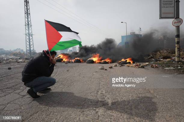 Palestinian protester holding Palestinian flag is seen in front of burning barricade as Israeli soldiers intervene in Palestinian demonstrators,...