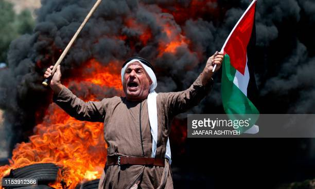 A Palestinian protester holding the national flag and a cane reacts during clashes with Israeli forces following a demonstration against against the...