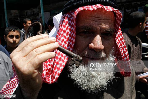 "Palestinian protester holds a key during a rally marking the ""Nakba"" in Rafah town in the southern Gaza Strip. Nakba means in Arabic ""catastrophe"" in..."