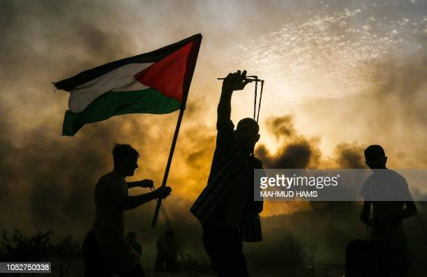 Palestinian protester holds a national flag as another protester throws a stone towards Israeli forces during a demonstration on the beach near the...
