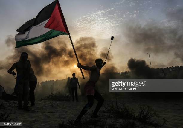 A Palestinian protester holds a national flag as he throws a stone towards Israeli forces during a demonstration on the beach near the maritime...
