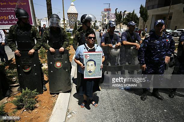 Palestinian protester holds a poster bearing a portrait of Palestinian prisoner Bilal Kayed during a demonstration of supporters of the Popular Front...