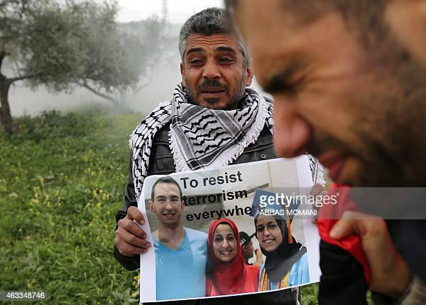 A Palestinian protester holds a poster showing three young Muslims who were killed in the US during a protest by Palestinians against terrorism on...