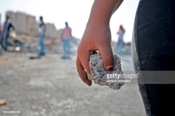 Palestinian protester holds a stone during clashes with Israeli forces in Ramallah near the Jewish settlement of Beit El in the occupied West Bank in...