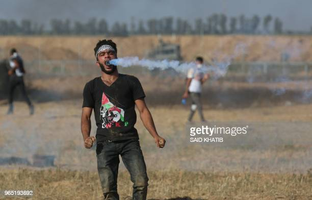 A Palestinian protester holds a tear gas canister in his mouth during a demonstration along the border with Israel east of Khan Yunis in the southern...