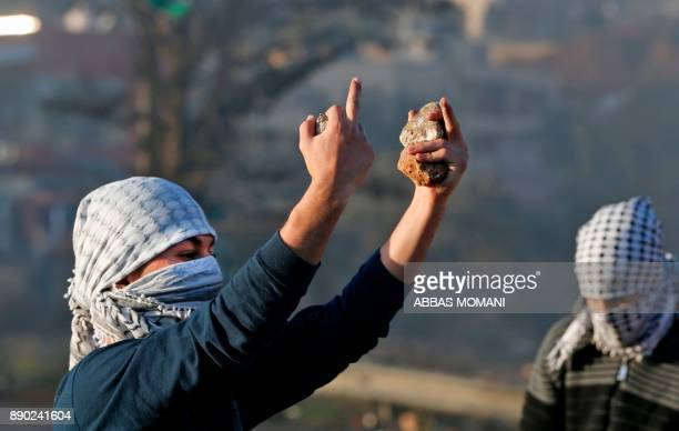 A Palestinian protester holds stones as he gestures with his middle fingers at Israeli forces during clashes in the West Bank city of Ramallah on...