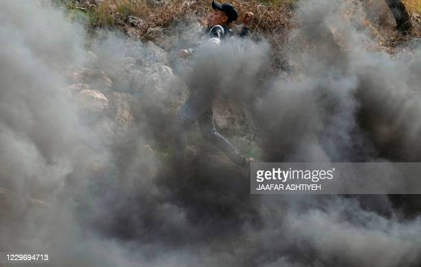 A Palestinian protester hurls rocks amid billowing smoke during clashes with Israeli security forces following a demonstration against the expansion...
